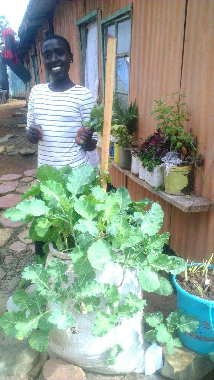 A lady stood with vegetables grown in her garden
